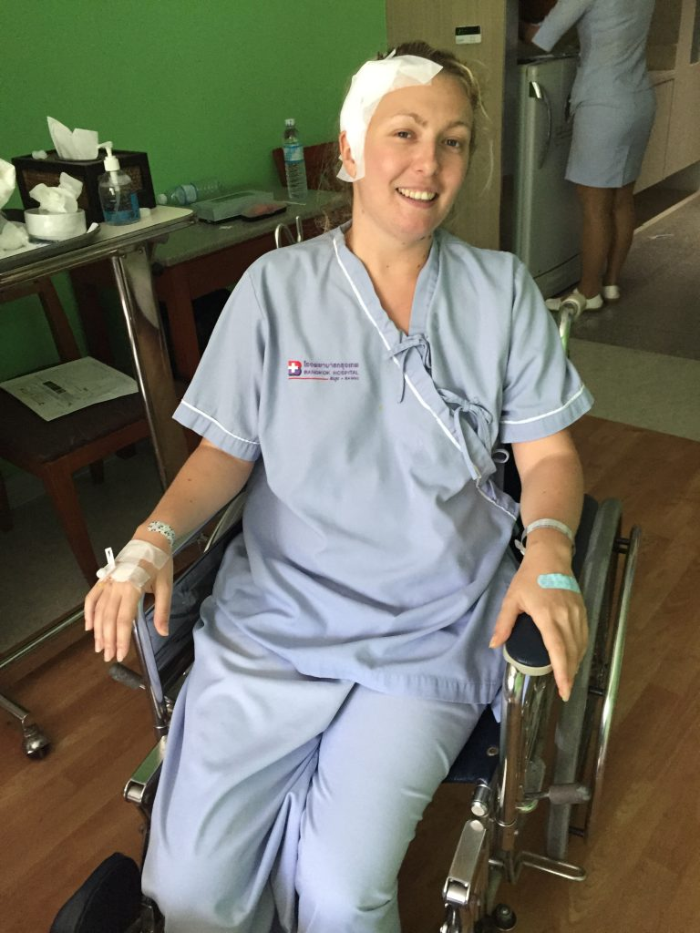 Jem Ayres in a wheelchair in hospital after receiving treatment for her brain tumour.